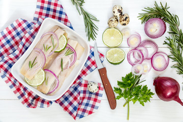 Sliced herring fillets, cut onion and lime on white plate. Checkered napkin. On wooden table.