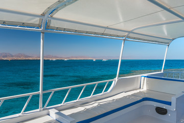 View at the coral sea from a white yacht. Perfect place for snorkeling. Summer vacation at sea with turquoise clear water.