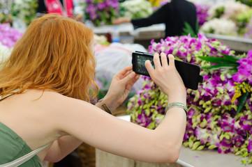 Girl tourist photographing smartphone flower market tour