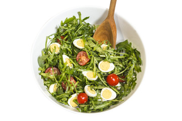 Quail eggs salad in a bowl with a wooden spoon