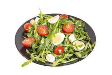 Quail eggs salad on a dark plate