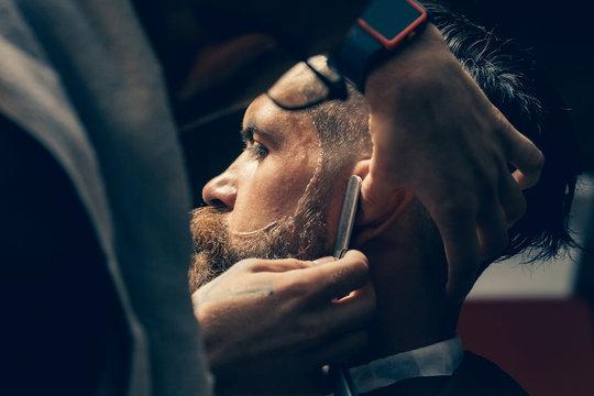 Bearded man with long beard getting hair shaving with razor