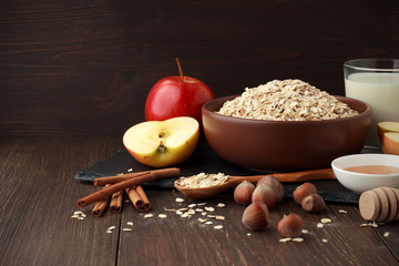 Still life of ingredients for healthy diet: oat flakes in bowl with apple, cinnamon, nuts, honey, milk on wooden table.
