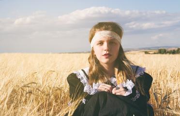 Mujer joven y rubia en los campos de trigo en verano