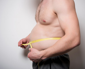 man measures the abdomen with a tape measure