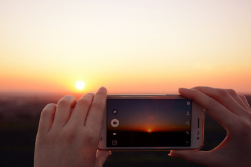 Photographing the sunset with smartphone in the hands