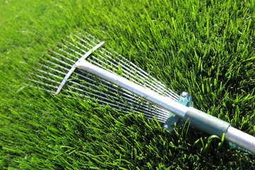 Adjustable steel fan rake for leaves and grass lying on the fresh mown lawn grass in the summer garden