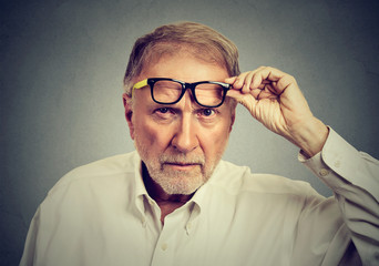 Skeptical senior man with glasses looking at you