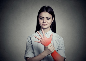 Woman holding her painful wrist colored in red