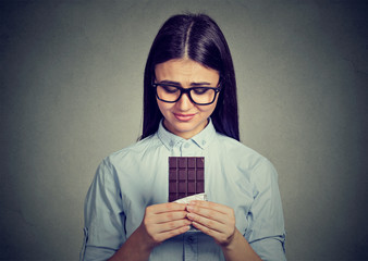 Sad woman tired of diet restrictions craving sweets chocolate bar