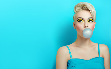 Fashionable girl with a stylish haircut inflates a chewing gum. The girl in the studio on a blue...