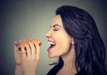 Side profile young woman eating a tasty burger .