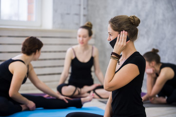 Women practicing yoga at health club. Young girls talking and relaxing after fitness, Yoga instructor speaks on the phone after training, lifestyle concept