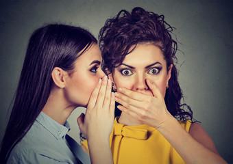 shocked woman listening gossip a secret in the ear