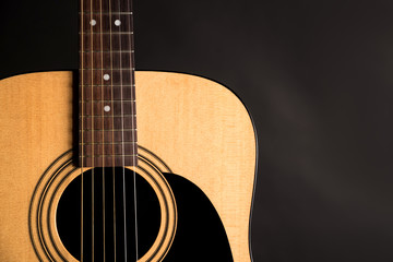 Part of a wooden acoustic guitar on the left side of the frame, on a black isolated background