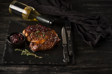 Steak and wine bottle with herbs on black stone plate. Black table background with copy text area for menu design. Horizontal top view.