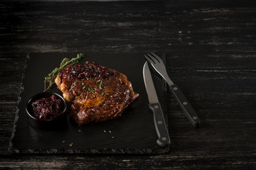 Beef steak on black stone plate. Black table background with copy text area for menu design. Horizontal top view.