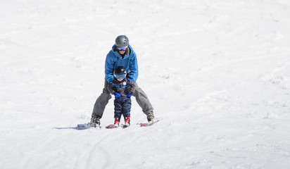 Toddler Boy Skis Downhill with the Help of His Father. Dressed Safely with Helmet and Harness.
