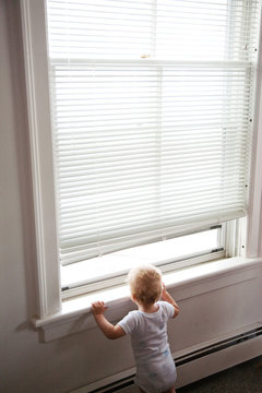 11 month old baby boy looking out window under blinds