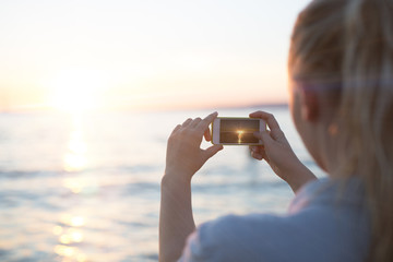 Woman taking a photo of a beautiful sunset in Marseille in France.