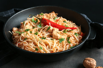 Frying pan with delicious chicken spaghetti on table