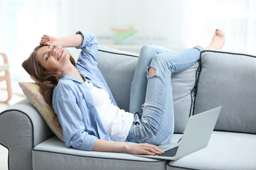 Beautiful young woman with laptop resting at home