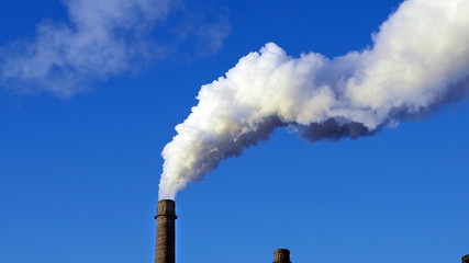 Factory plant smoke stack over blue sky background. Energy generation and air environment pollution industrial scene.