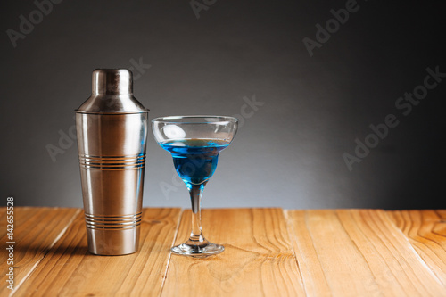 Cocktail shaker and drink on wooden table on dark for Sur la table cocktail shaker