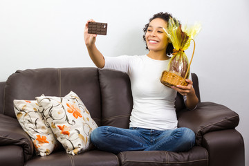 Beautiful woman is photographing herself with chocolate easter egg.