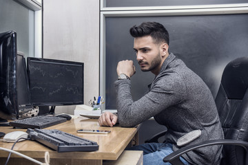 Attractive young businessman sitting at desk in his office working with computer