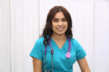 Portrait of a young attractive hispanic female healthcare worker, nurse on white background with copy space
