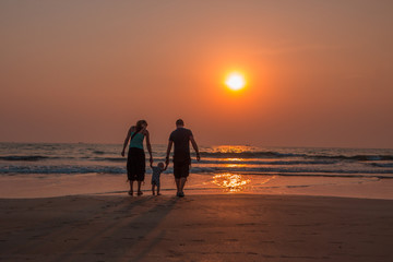 Happy family together, parents with their little child at sunset. Arambol beach, North Goa, India