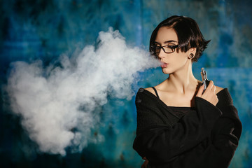 A girl with glasses vaping and releases a cloud of vapor. Model in a black vaper smoke vaporizer on a turquoise background