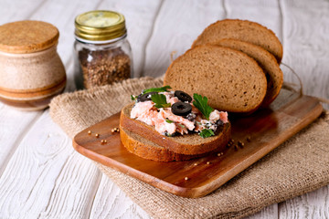 Smoked salmon and soft cheese spread, mousse, pate on a bread with olives and parsley