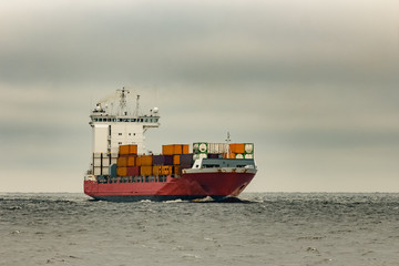 Red cargo container ship sailing from Baltic sea in cloudy day