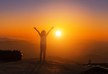 silhoutte young asian women stand raised up arms enjoying to valley view on high cliff  from top of mountain  on sunset