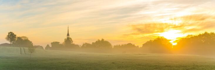 Foto op Aluminium Ochtendgloren Foggy morning in the field near the village, panorama