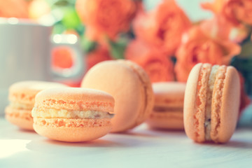 Orange mango or citrous macaroons and orange fresh little roses on light wooden background. Coloring and processing photo with light vintage style. Toned. Shallow depth of field.