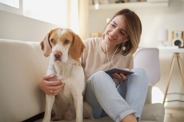 Beautiful Caucasian businesswoman taking break from freelance work, using tablet device and playing her dog