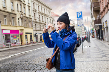 Woman tourist in a European city takes pictures on a smartphone