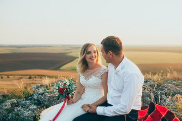 Beautiful bride and groom embracing each other in the mountains. Very beautiful white wedding dress designer. Beautiful couple in love on the rocks. Sunset