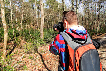 Photographer in the forest. Guys in nature photography forest environment, enjoying the beautiful spring day. Man photographer taking photo of nature. Horizontal shape, side view, copy space.