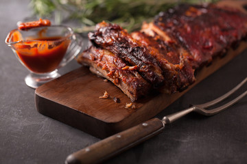 Delicious barbecued ribs seasoned with a spicy basting sauce and served with chopped fresh vegetables on an old rustic wooden chopping board in a country kitchen