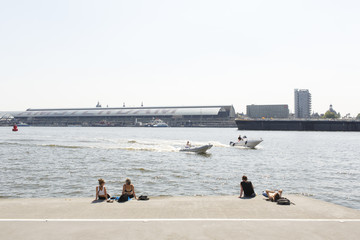 People enjoying the waterfront view at the water of the IJ in Amsterdam.Central station in the background.