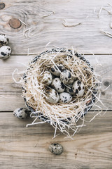 easter quail eggs in the nest on the old rustic wooden table background, flat lay