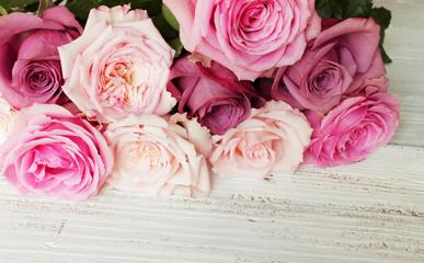 Rosafarbene Rosen auf weißem Holz
