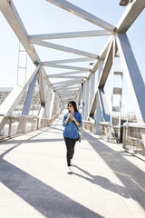 Spain, Barcelona, smiling young woman with beverage walking on a bridge