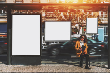 Curly beautiful brunette woman in sunglasses and yellow coat holding digital tablet while sitting and waiting her bus inside of glass city bus stop, with several blank mock-up billboards around her Fotomurales