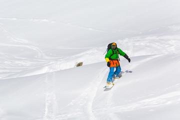 snowboarder snowboarding on fresh snow on ski slope on Sunny winter day in the ski resort in Georgia
