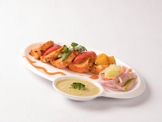 Paneer tikka with mint yogurt chutney served in a white plate on white background